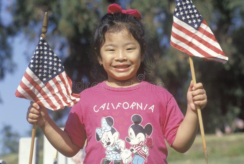 Ein Philippinisch-Amerikanische Mädchenholding Amerika-Markierungsfahnen stockfotos