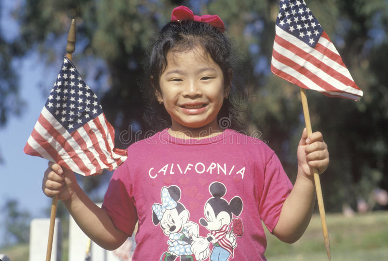 Ein Philippinisch-amerikanisches Mädchen, das Amerika-Flaggen, Los Angeles, CA hält stockbild