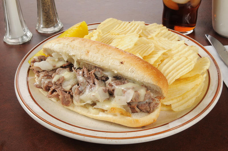 Philly Käse-Steaksandwich mit Chips lizenzfreies stockfoto