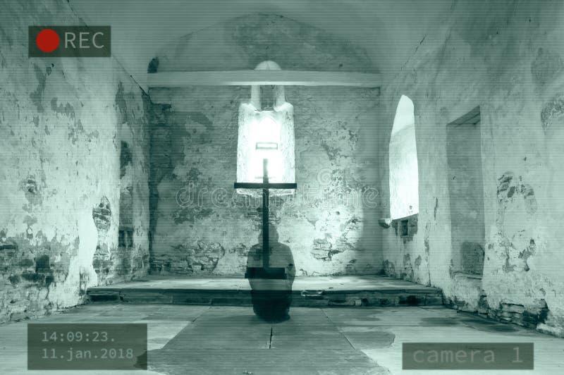 Ein Photoshop eines CCTV-Bildes eines mit Kapuze Geistes, der nahe bei einem Kreuz in einer veralteten Kirche knit stockfotografie