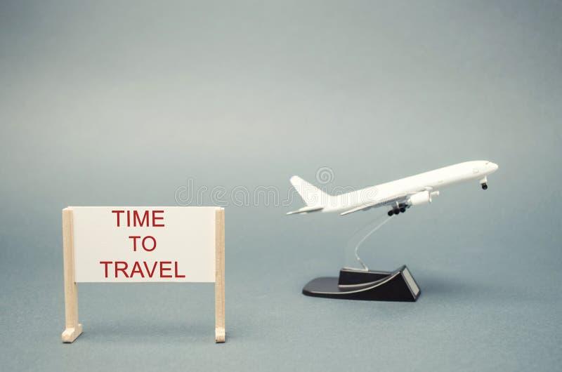 Ein Plakat mit der Wörter Zeit zu reisen und einem Miniaturflugzeug Das Konzept der Planung Sommer- oder Winterferien Familienres stockfotografie