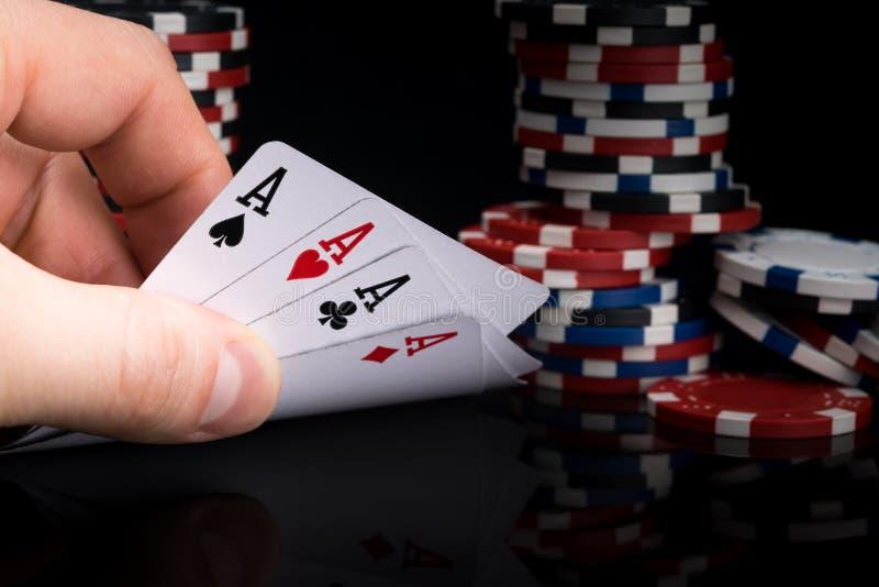 Ein Pokerspieler betrachtet seine Karten, indem er sie auf einer schwarzen Tabelle vor dem hintergrund der Stapel Pokerchips anhe stockbild
