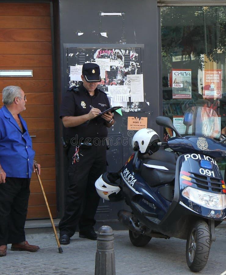 Ein Polizeibeamte stellt ein Dokument auf der Verletzung auf den Straßen von Sevilla auf stockfotografie