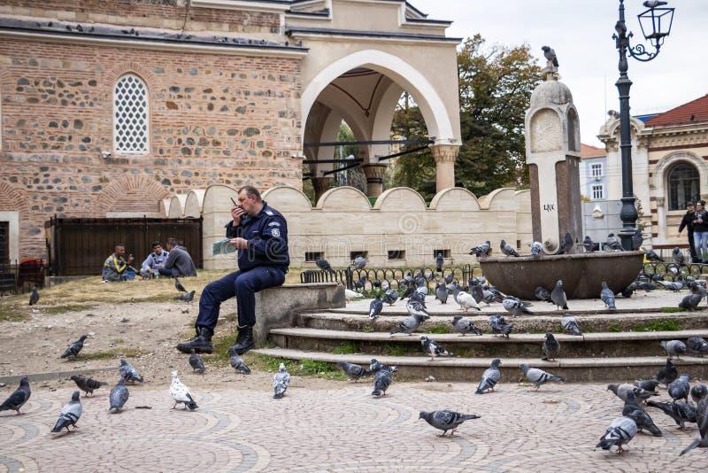 Ein Polizist sitzt nahe Brunnen im Nichtgebrauch, der mit Tauben gedrängt wird und Gespräche auf dem Radio, drei fremde junge Män stockbild