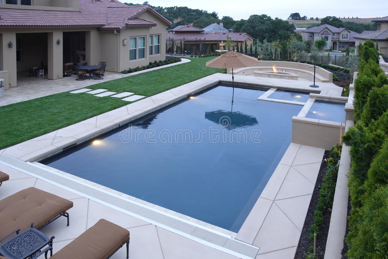 Ein Pool mit einem Wasserfall in einem Luxuxhinterhof stockfotos