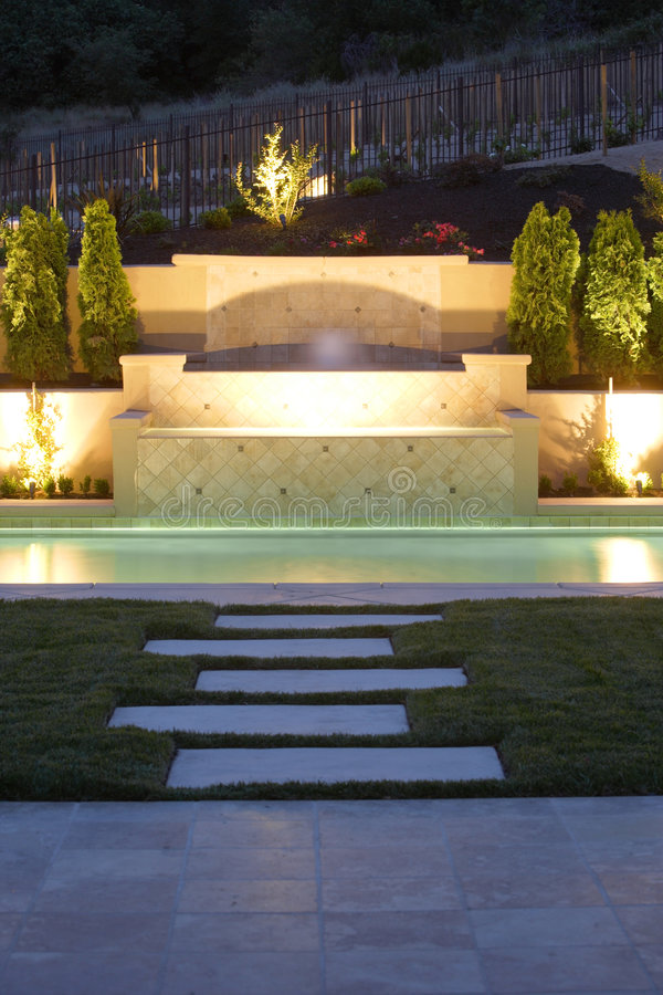 Ein Pool mit einem Wasserfall in einem Luxuxhinterhof lizenzfreie stockbilder