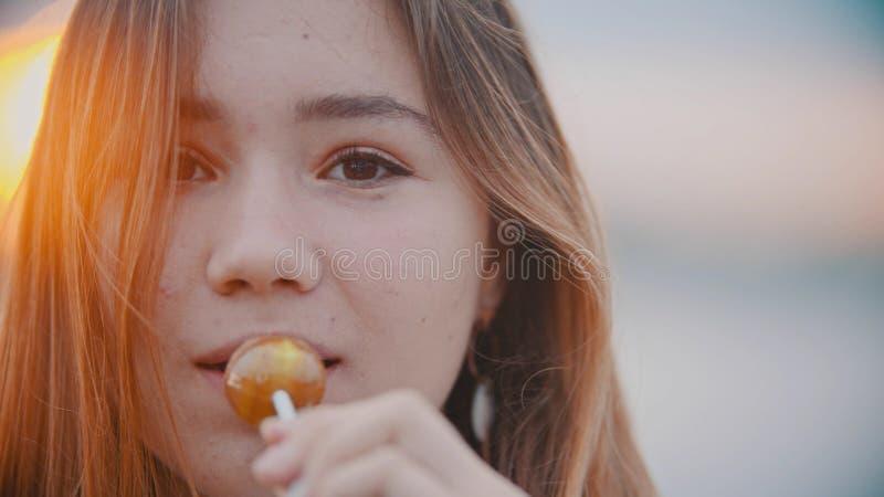 Ein Porträt der Jugendlichen schauend in der Kamera und einen Lutscher auf Sonnenuntergang essend lizenzfreies stockfoto