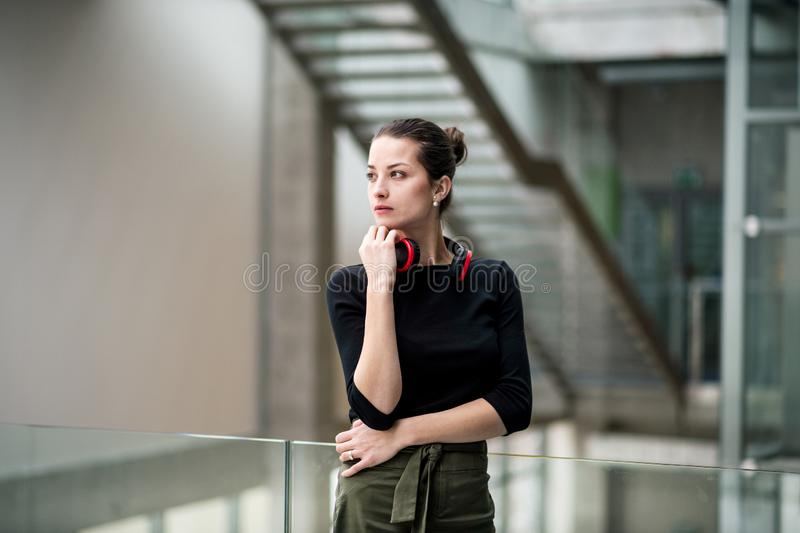 Ein Porträt der jungen Geschäftsfrau mit den Kopfhörern, die im Korridor außerhalb des Büros stehen stockbild