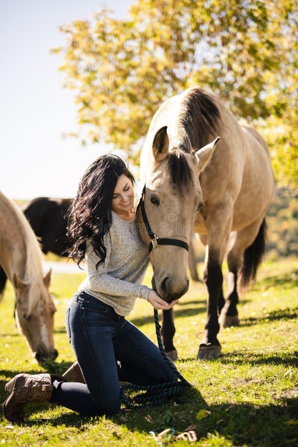 Ein Porträt der jungen Schönheit mit braunem Pferd draußen lizenzfreie stockfotos