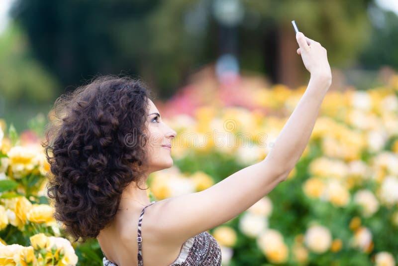 Ein Porträt der kaukasischen Frau mit dem dunklen gelockten Haar, das selfie nahe gelben Rosenbusch in einem Rosengarten nimmt lizenzfreie stockfotos