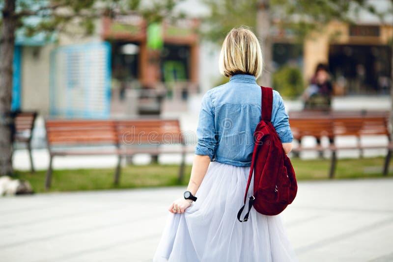 Ein Porträt der Rückseite eines Mädchenholding marsala Rucksacks, der blaues Denimhemd und grauen Tulle-Rock trägt Ein Mädchen ge lizenzfreies stockfoto
