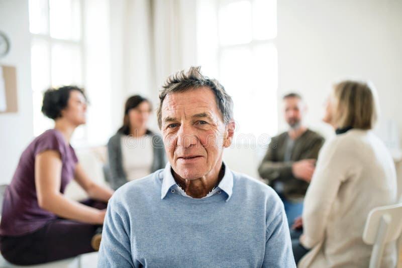 Ein Porträt des älteren deprimierten Mannes während der Gruppentherapie lizenzfreies stockbild