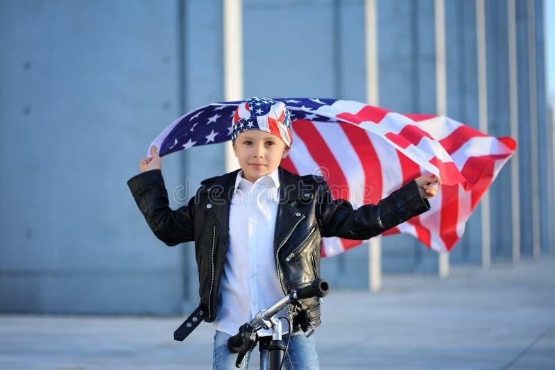 Ein Porträt des amerikanischen Jungen sitzend auf wellenartig bewegender amerikanischer Flagge des Fahrrades stockfotos