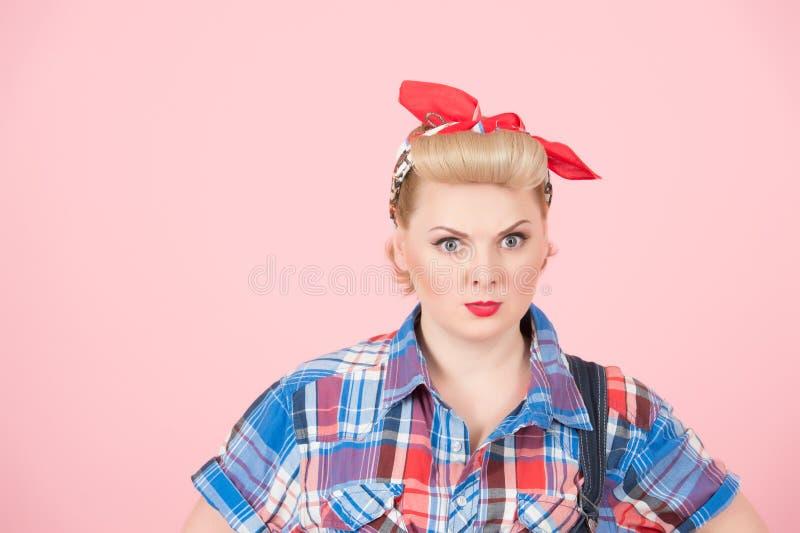 Ein Porträt des blonden Lockenpin-up-girl mit rotem Kopftuch Stilvolles schönes Make-up auf rosa Hintergrund Starke weibliche Ans stockfoto