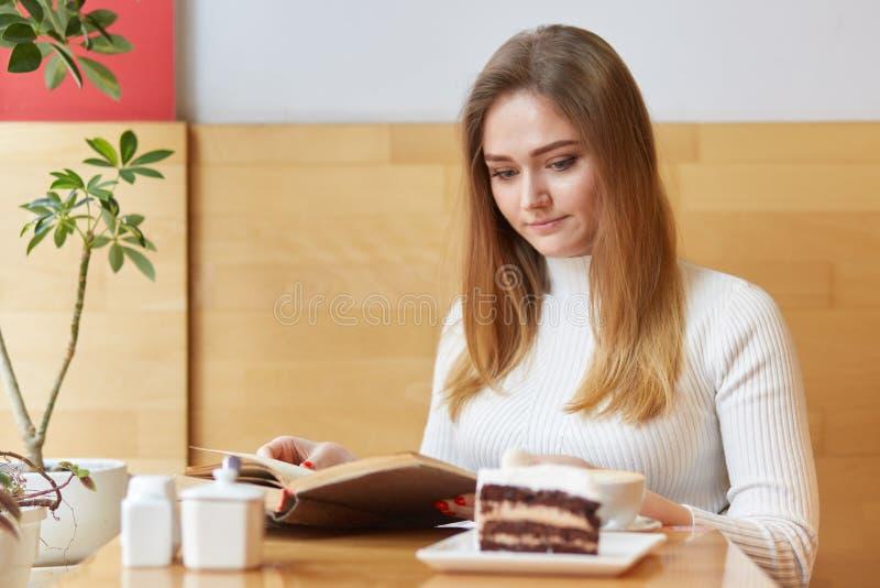 Ein Porträt des ernsten attraktiven Mädchens sitzt im lokalen Café und liest altes Buch, trägt weiße Kleidung Angemessene behaart stockfoto