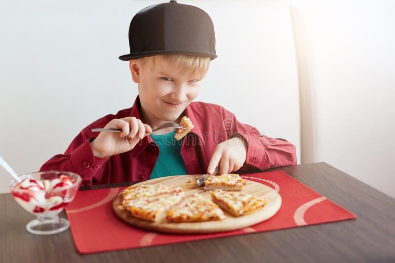 Ein Porträt des hübschen Kindermannes kleidete im stilvollen roten Hemd und in der schwarzen Kappe die Pizza und Eiscreme essend  lizenzfreies stockbild
