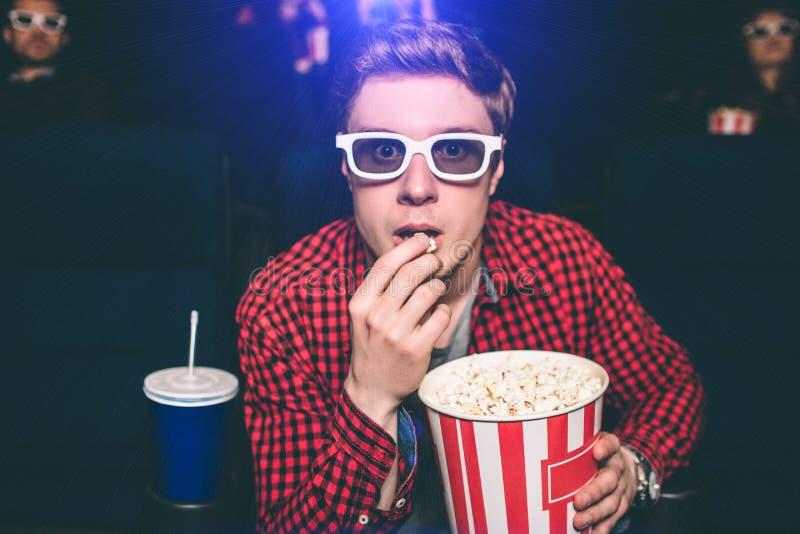 Ein Porträt des Kerls sitzend im Stuhl in der Kinohalle und Popcorn essend Er schaut gerade sehr intensiv Kerl trägt stockfotografie