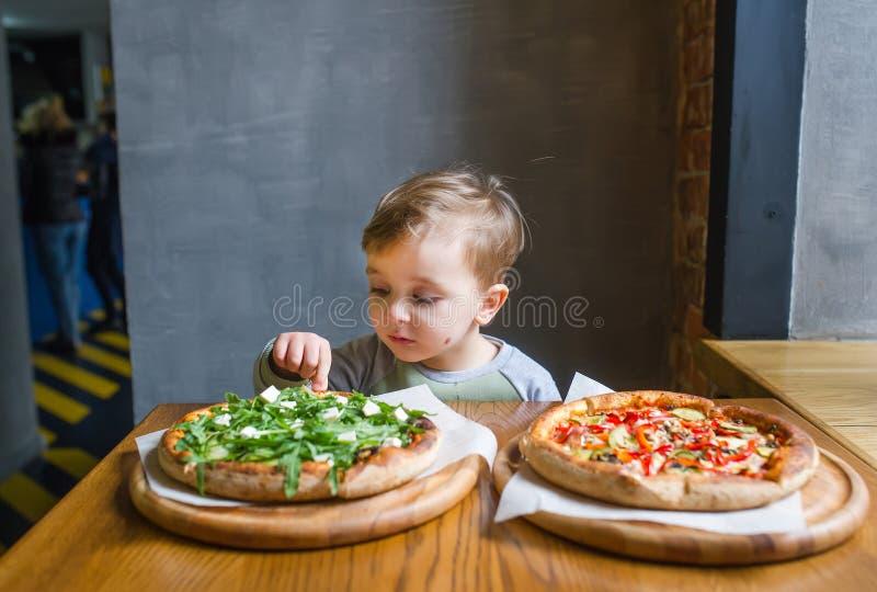 Ein Porträt des netten kleinen Jungen, der Pizza im Restaurant isst stockbild