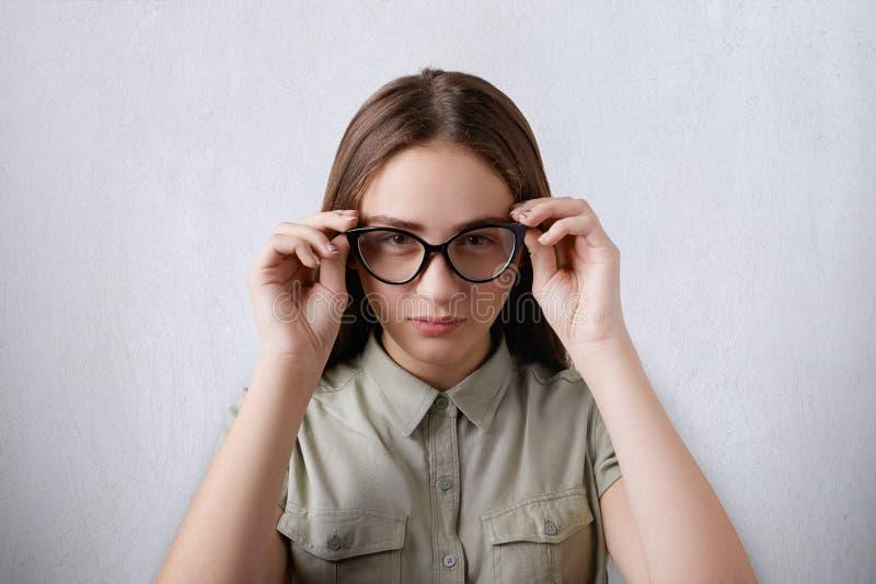 Ein Porträt des tragenden Hemdes des schönen Mädchens, welches das lange Haar lokalisiert über dem grauen Hintergrund trägt die g lizenzfreies stockbild