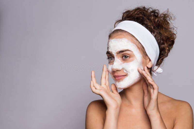 Ein Porträt einer jungen Frau mit Maske in einem Studio, in einer Schönheit und in einer Hautpflege lizenzfreie stockfotografie
