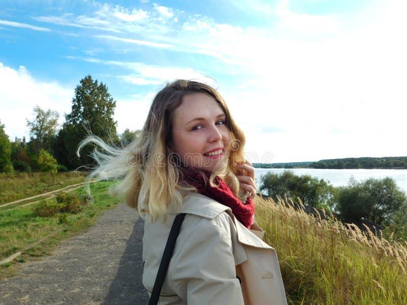Ein Porträt einer jungen lächelnden Frau Das Mädchen hat einen Weg auf einem Kai und dreht sich herum stockbilder
