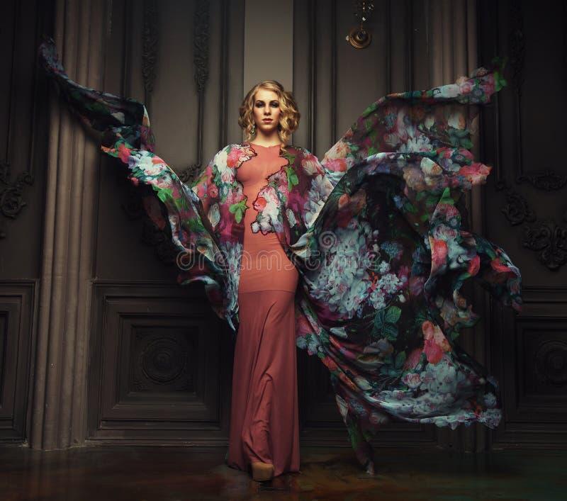 Ein Porträt einer schönen eleganten Frau im flatternden Luxuskleid lizenzfreies stockfoto