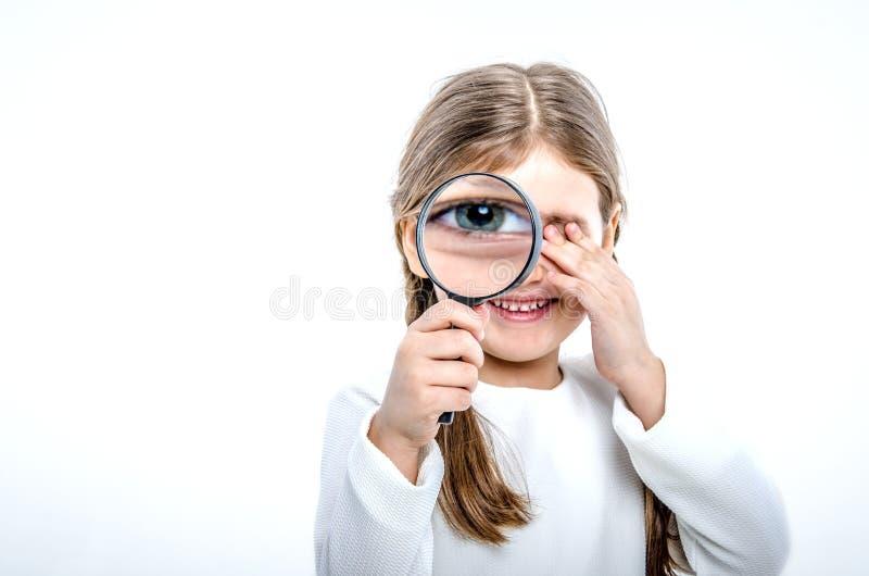 Ein Porträt eines kleinen Mädchens, das eine Lupe vor ihr hält stockbild