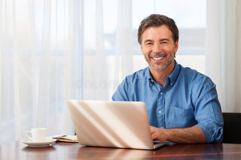 Ein Porträt eines lächelnden bärtigen Mannes von mittlerem Alter auf einem Fensterhintergrund lizenzfreies stockfoto