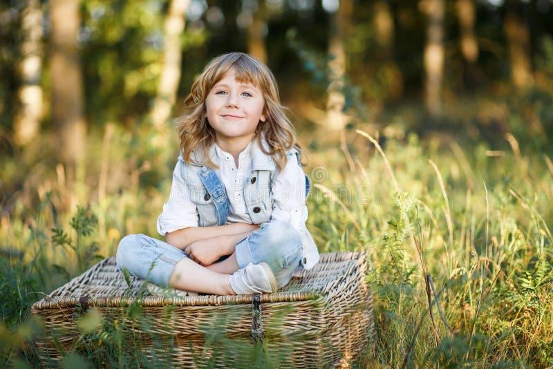 Ein Porträt eines netten kleinen Jungen mit blauen Augen und langen blonden dem Haar, die draußen auf einem Korb bei Sonnenunterg lizenzfreie stockbilder