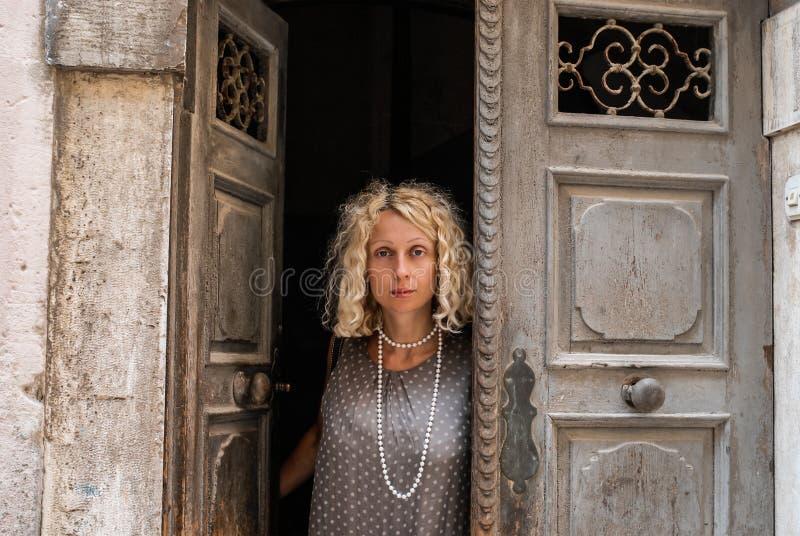 Ein Porträt jungen Blondine in einem neutralen grauen Kleid, stehend in einem Eingang einer schäbigen Tür stockbilder