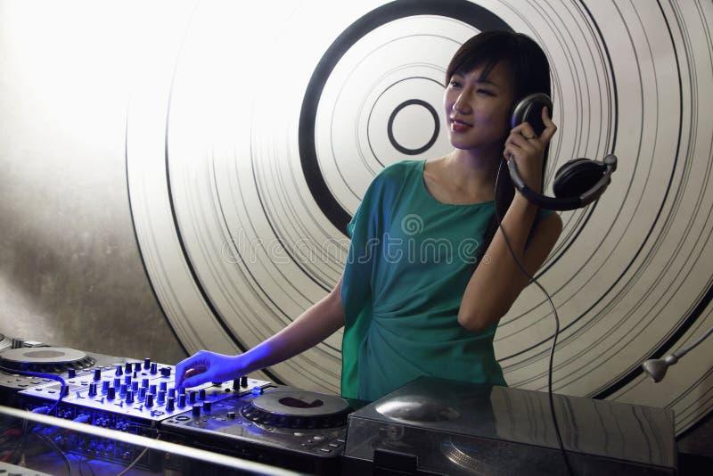 Ein Porträt von einem weiblichen DJ, das Musik in einem Nachtklub spielt stockbild