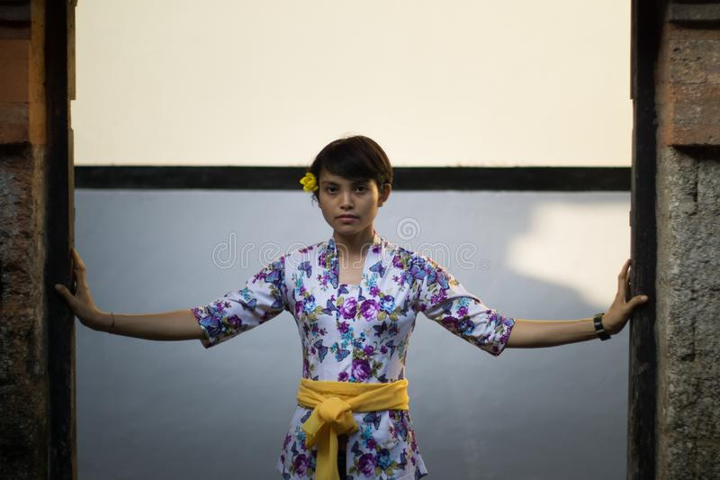 Ein Portr?t einer sch?nen kurzhaarigen Frau mit einer Blume auf seinem Ohr Sie tr?gt ein Bali-Kleid mit den Blumenmotiven und wir lizenzfreie stockfotos