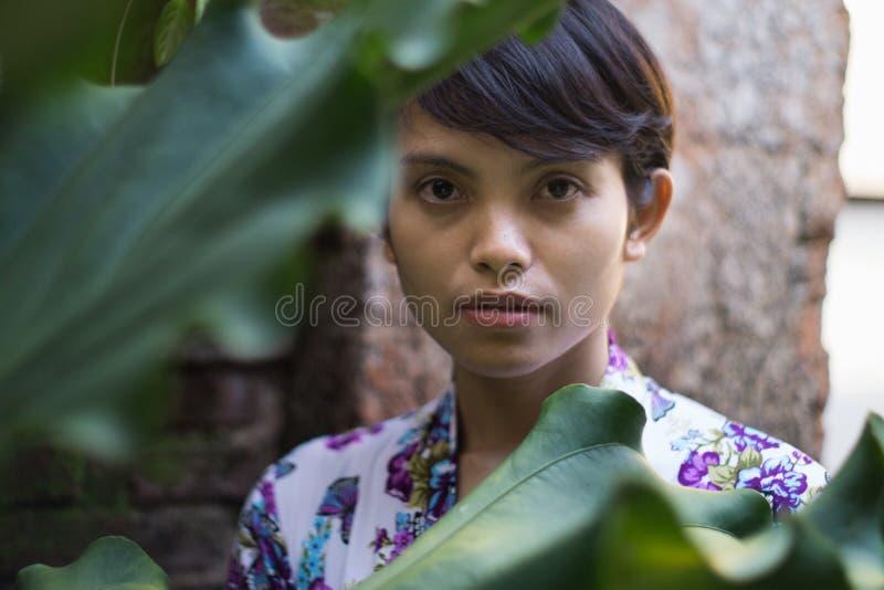 Ein Portr?t einer sch?nen kurzhaarigen Frau mit einer Blume auf seinem Ohr Sie tr?gt ein Bali-Kleid mit den Blumenmotiven und wir stockbilder