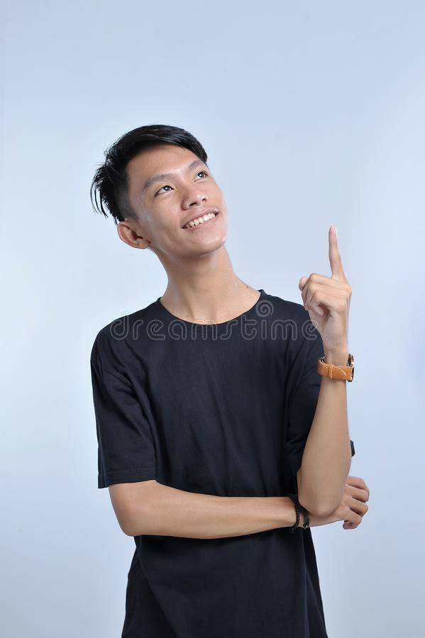 Ein Portr?t eines jungen asiatischen Mannes, der ein Ideenhandzeichen erh?lt Zeigen bis zum Kopienraum mit dem Zeigefinger ein gr lizenzfreies stockfoto