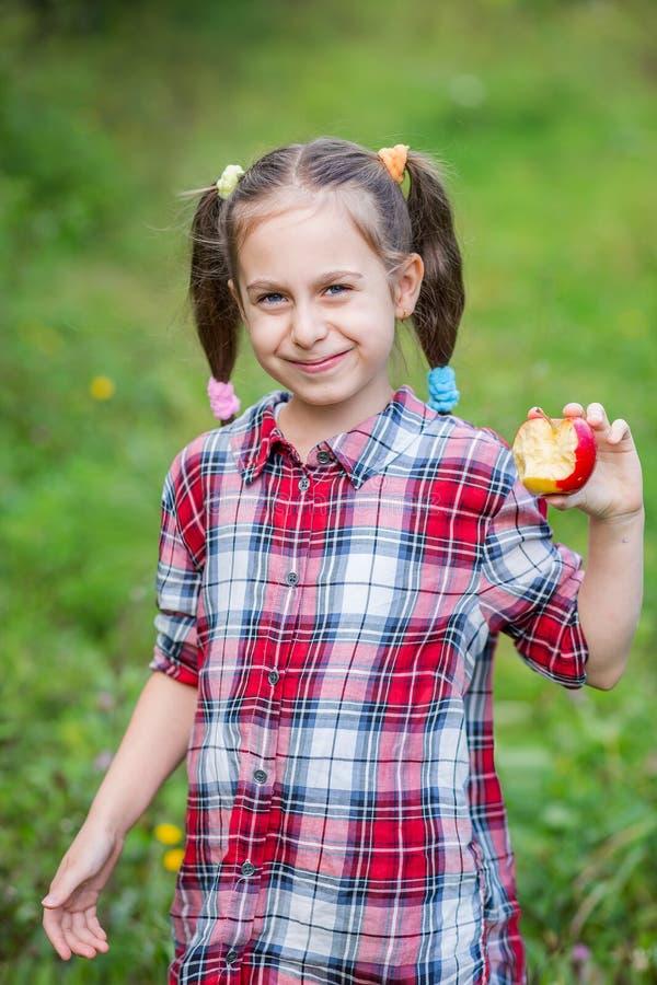 Ein Portr?t von einem netten M?dchen, das einen Apfel in einem Bauernhofgarten isst lizenzfreie stockfotografie