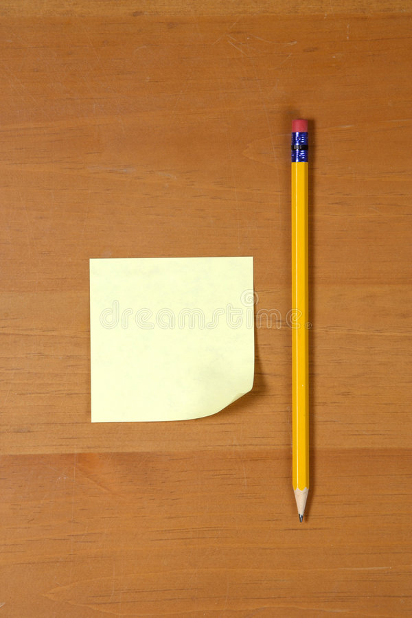 Ein Post-It auf einem hölzernen Schreibtisch lizenzfreies stockbild