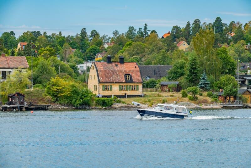 Ein privates Motorboot, das durch Häuser auf Skurusundet-Fluss überschreitet lizenzfreie stockbilder