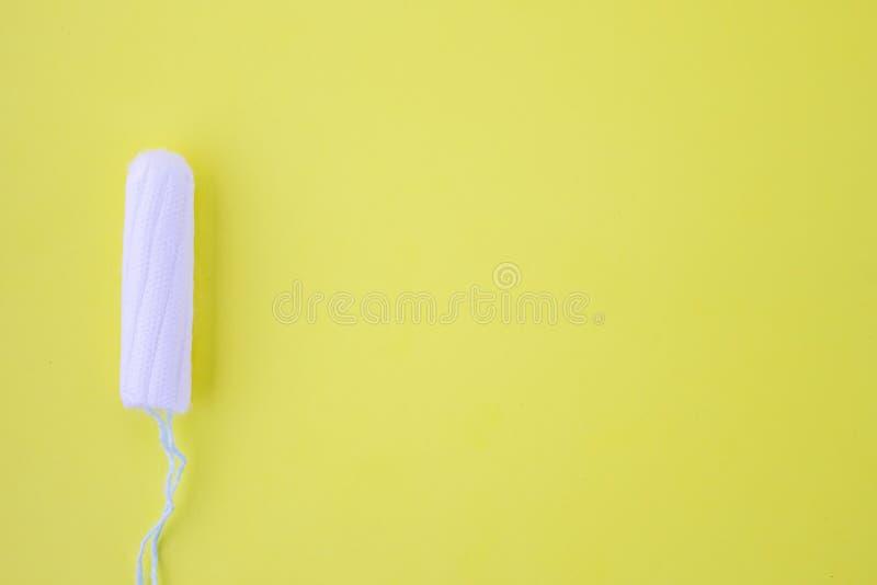 Ein Putzlappen mit Baumwolle auf einem gelben Hintergrund Das Konzept des Zeitraums des Menstruationszyklus Draufsicht, flache La lizenzfreies stockfoto