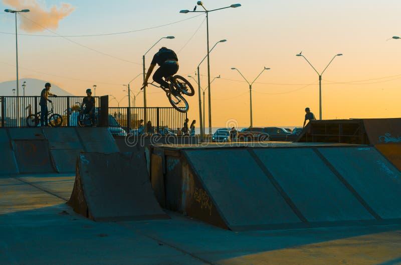 Ein Radfahrer auf jumpbox Sonnenuntergangtapete stockbild