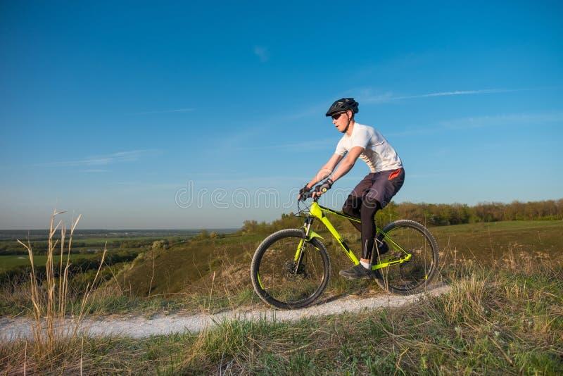 Ein Radfahrer in einem orange Hoodie reitet ein Fahrrad entlang einem Gebirgsweg Das Konzept des extremen Sports lizenzfreie stockbilder