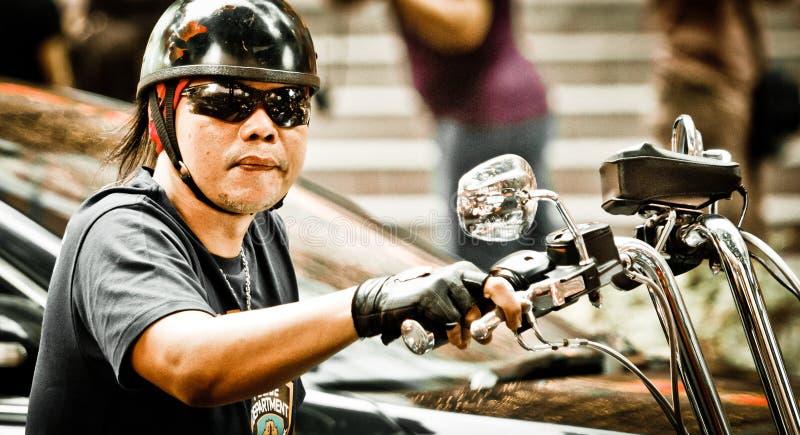 Ein Radfahrer tragende sunglass, die ein schwarzes Harley Davidson-Fahrrad reiten lizenzfreies stockbild