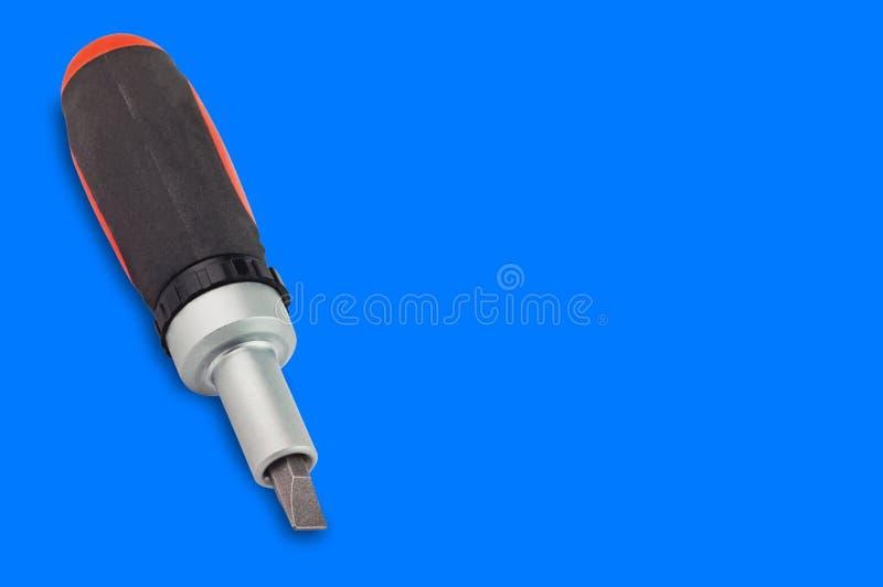Ein Ratschenschraubenzieher mit orange und schwarzem Plastik mit Gummigriff und St?ckchen auf blauem Hintergrund mit Kopienraum f lizenzfreie stockbilder