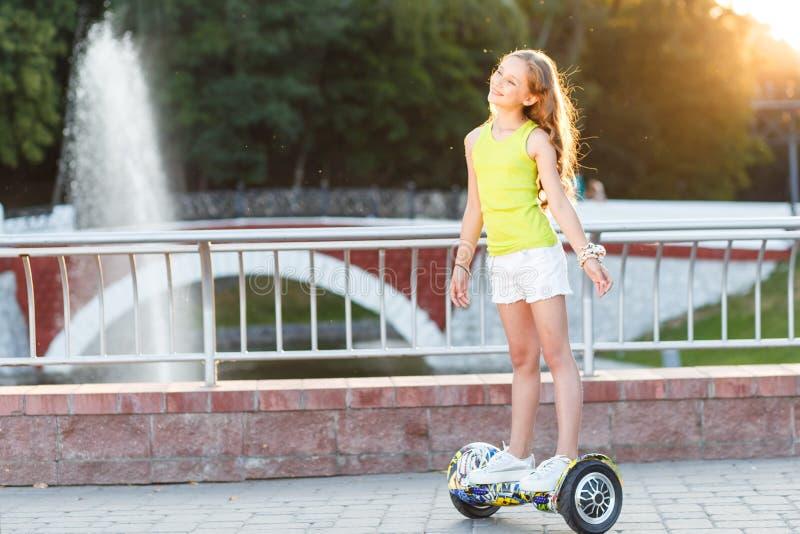 Ein recht glückliches Mädchenreiten auf Schwebeflug Brettern oder gyroscooters draußen bei Sonnenuntergang im Sommer Berufslebenk stockfotos