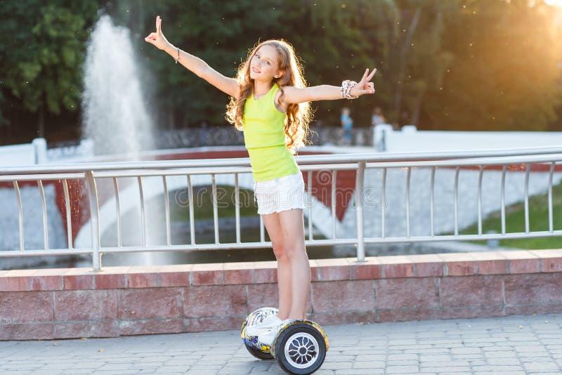 Ein recht glückliches Mädchenreiten auf Schwebeflug Brettern oder gyroscooters draußen bei Sonnenuntergang im Sommer Berufslebenk lizenzfreies stockbild