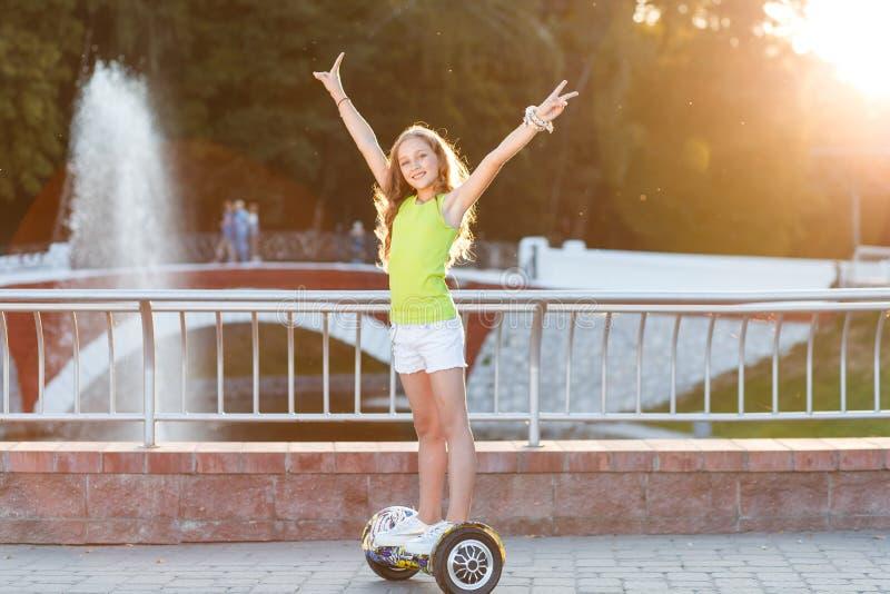 Ein recht glückliches Mädchenreiten auf Schwebeflug Brettern oder gyroscooters draußen bei Sonnenuntergang im Sommer Berufslebenk stockfoto
