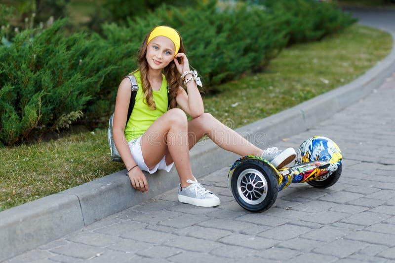 Ein recht glückliches Mädchenreiten auf Schwebeflug Brettern oder gyroscooters draußen bei Sonnenuntergang im Sommer Berufslebenk stockbild