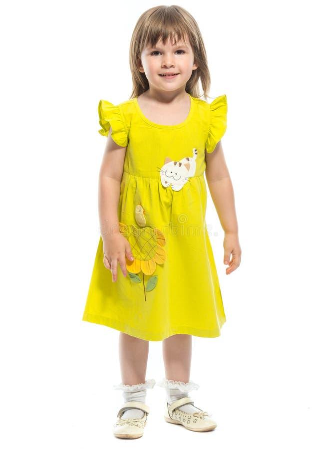 Ein recht kleines Mädchen in einem gelben Kleid stockbilder