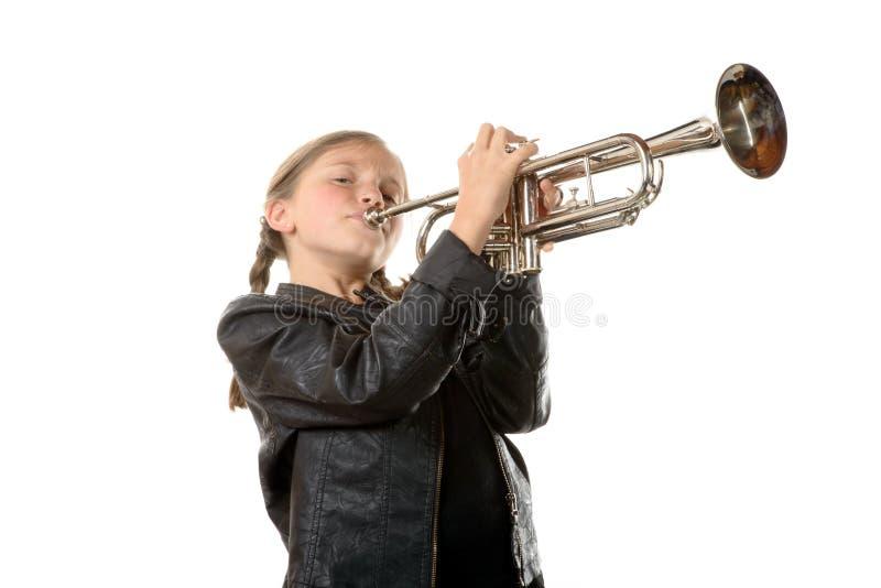 Ein recht kleines Mädchen mit einer Schwarzjacke spielt die Trompete lizenzfreies stockfoto