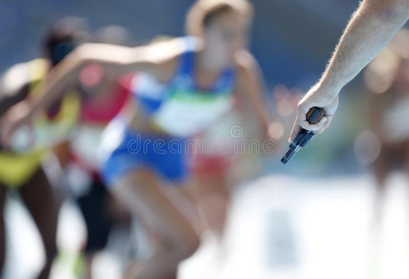 Ein Referent feuert die Starterpistole für die Läufer eines Bahnrennens ab lizenzfreies stockbild