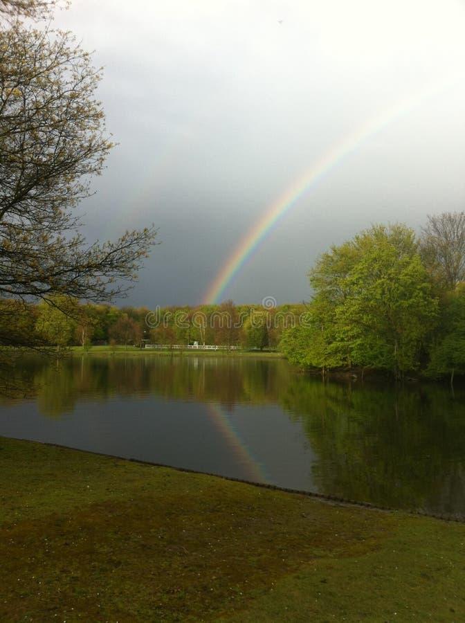 Ein Regenbogen mit Reflexion über dem See Umminger, Deutschland stockfotos